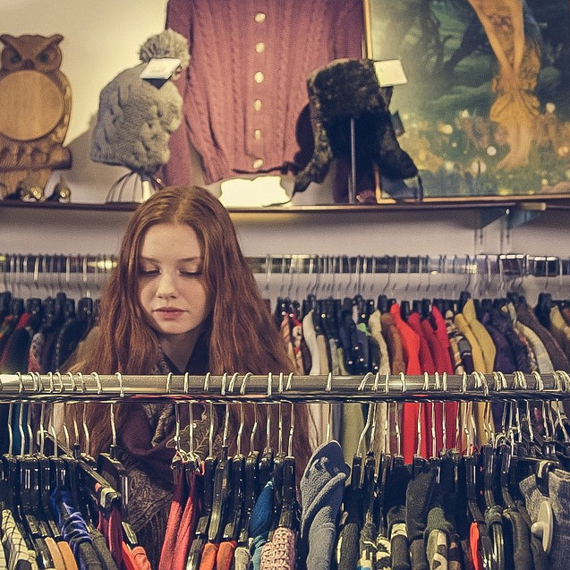 Person browsing a charity shop clothes rail
